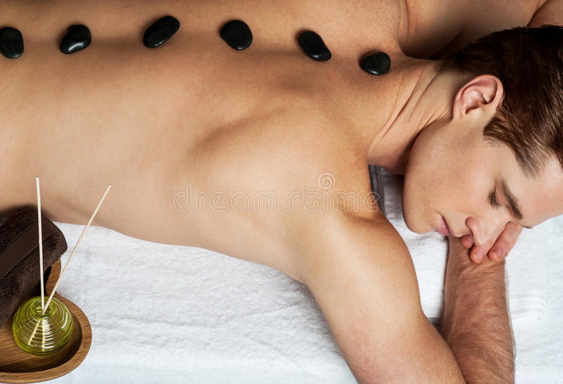 Man in spa salon with hot stones royalty free stock images