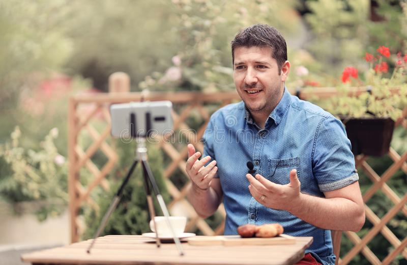 Man speaking in front of camera with attached mic lavalier. Vlogger man sitting on a table and making a vlog episode stock photo