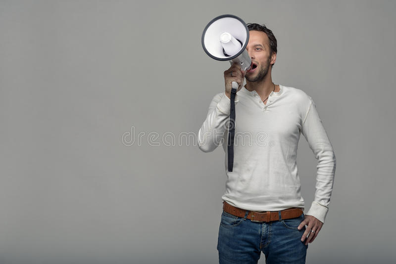 Man speaking over a megaphone. As he makes a public address, participates in a protest or organises a rally or promotion, over grey with copy space to the side royalty free stock image