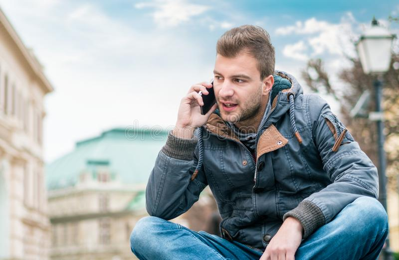 Man speaking over phone while sitting, serious guy on phone. Outdoor stock photos