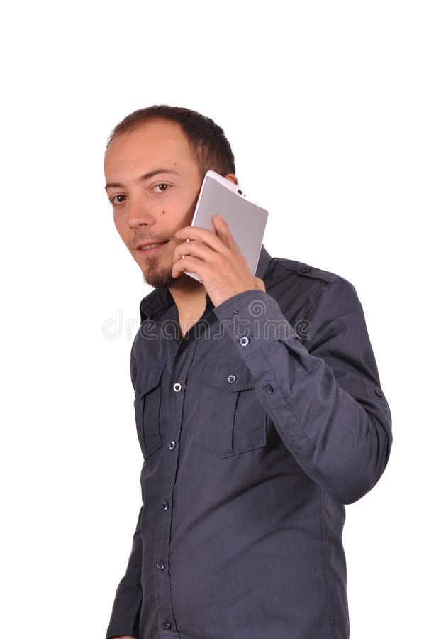 Man is speaking on smartphone and smiling. Young attractive guy in elegant shirt is speaking on his smartphone. White background stock photography