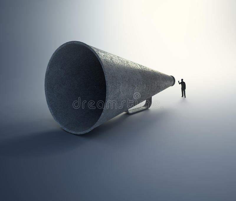 Man speaking through a vintage megaphone. A tiny man speaking through a vintage megaphone royalty free stock photo