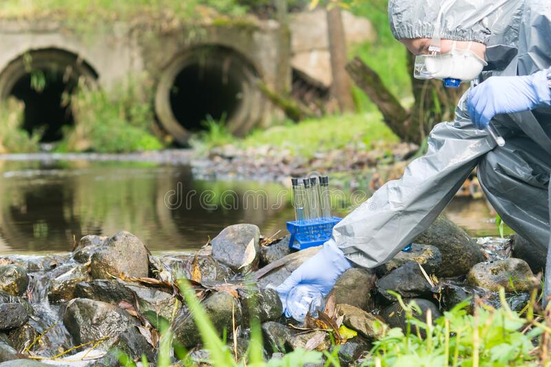 A man in special protective clothing and a mask draws water from a river into a flask after discharges into the river, checking royalty free stock photo