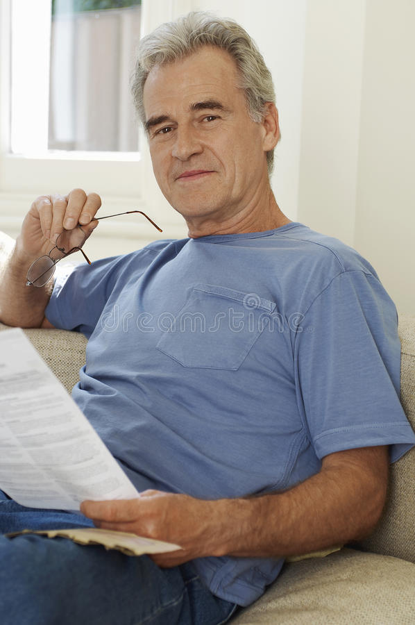 Man With Spectacles And Bill Sitting On Sofa stock photography