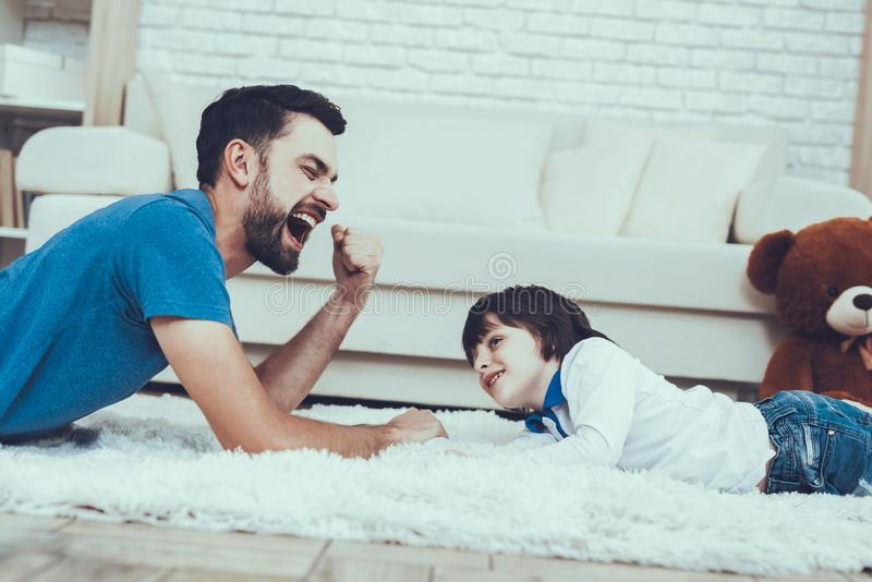 Father and Son is Playing in Arm wrestling. Man Spends Time with His Son. Father of Boy is Engaged in Raising Child. Father and Son is Playing in Arm wrestling stock image