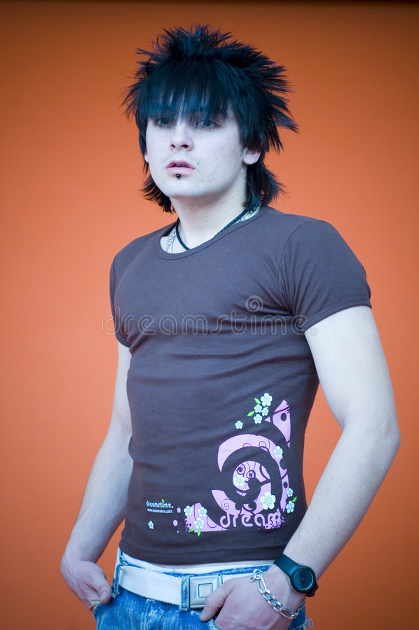 Man with Spiky Hair. Young man with dreamstime shirt and spiky hair, standing with hands in pockets, seen from waist up, orange background stock photo