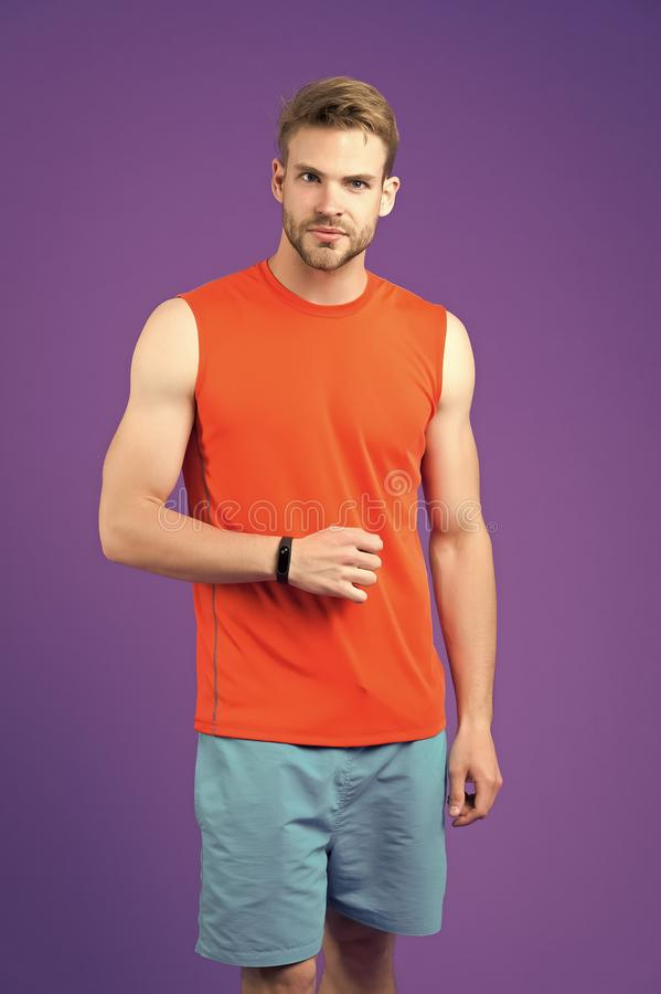 Man with sport smartwatch on violet wall. Sportsman in orange vest and blue shorts. Fashion accessory for training and. Workout. New technology for healthy royalty free stock photo