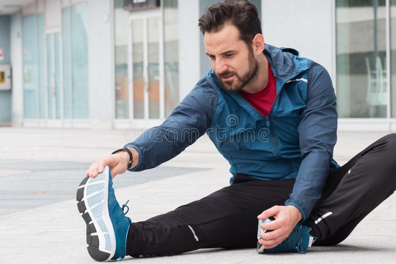 Man with sportive clothes doing leg stretches exercises royalty free stock image