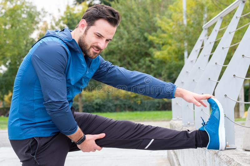 Man with sportive clothes doing leg stretches exercises stock images