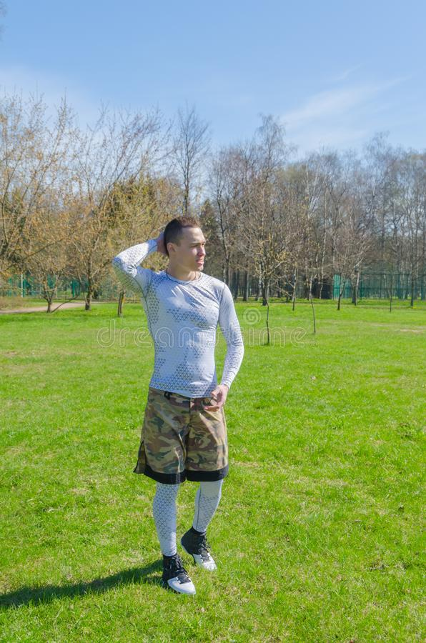 A man in sports clothes in the summer, trains in the Park royalty free stock photography