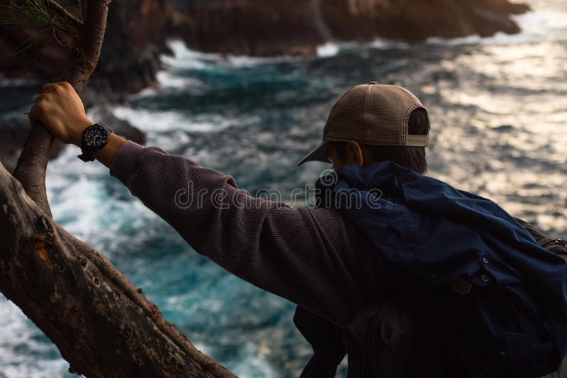 Man In Sports Gear Holding On Tree Branch Looking At Body Of Water Below Free Public Domain Cc0 Image