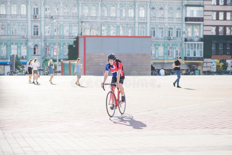 Man in sports wears a red bicycle in the city with a background of people and architecture stock photo