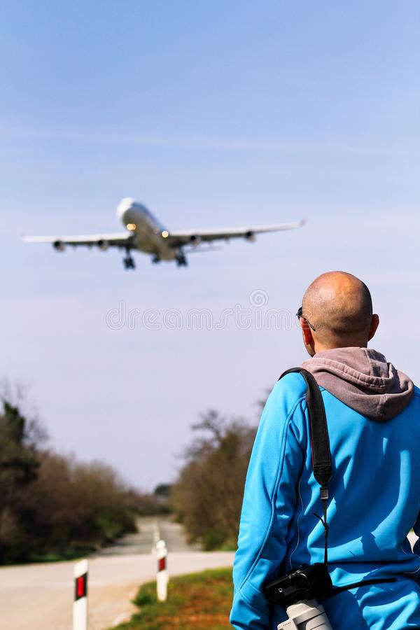 Man is looking at the plane which is landing stock photo