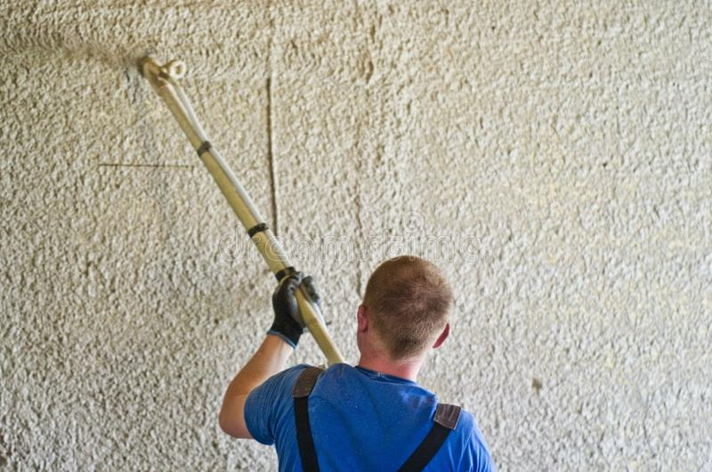 Man spraying concrete stucco to wall royalty free stock images
