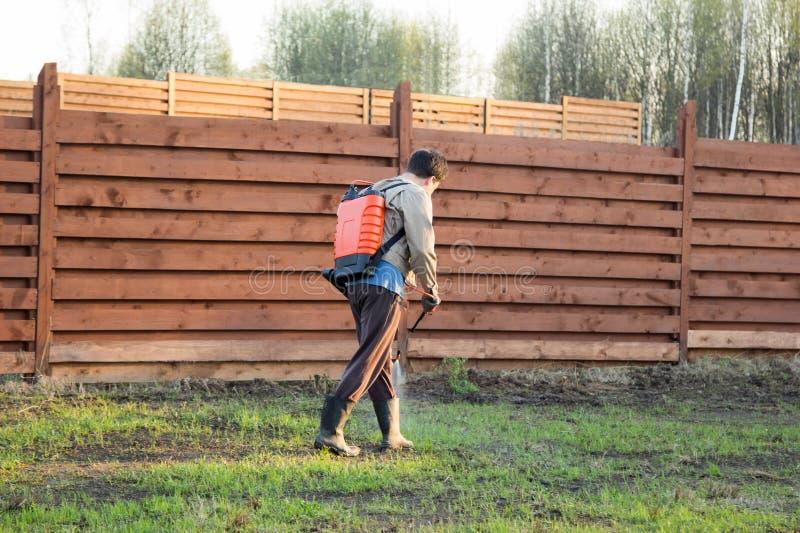 Man sprays grass with herbicide of a knapsack sprayer. Man sprays grass with herbicide of knapsack sprayer royalty free stock photography