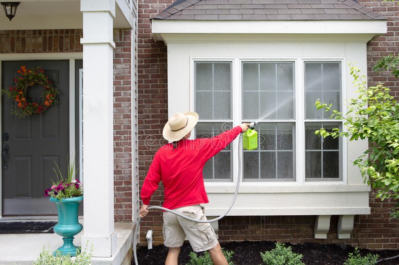 Man spring cleaning the exterior of his house. Washing down a bay window, with a high pressure sprayer attached to a hose pipe in a close up rear view stock photos