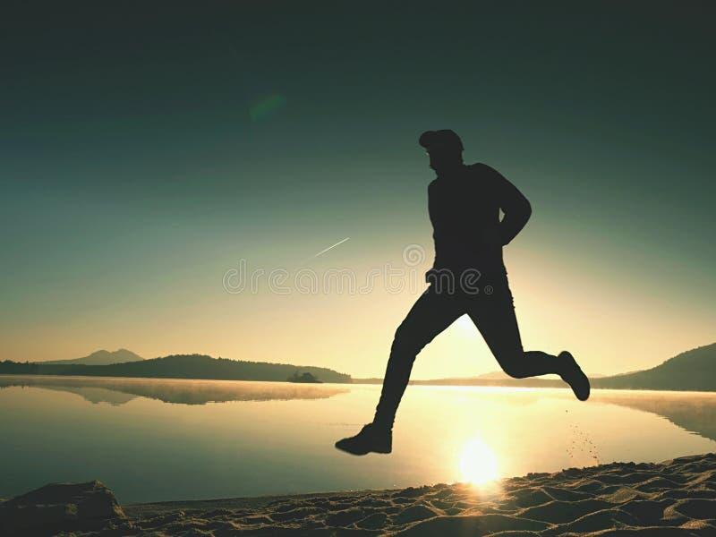 Man spring på stranden mot bakgrunden av en härlig solnedgång Sand av bergsjön royaltyfri foto