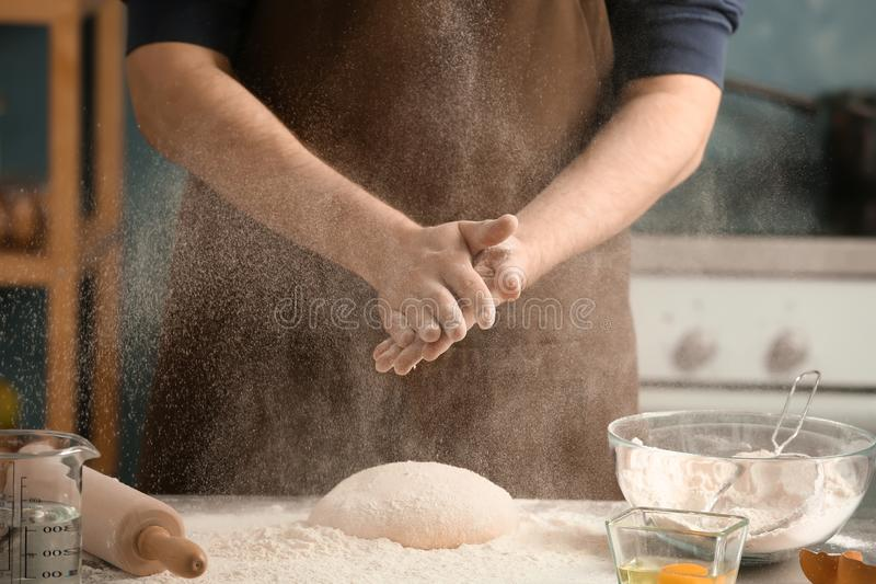 Man sprinkling flour over dough on table stock image