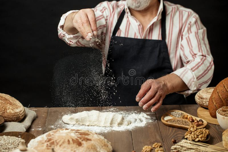 Man sprinkling some flour on dough. Hands kneading dough, cropped view. Man in black apron sprinkling some flour on dough isolated over dark studio background stock images