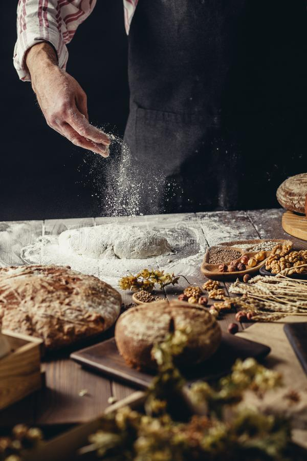 Man sprinkling some flour on dough. Hands kneading dough, cropped view. Man in black apron sprinkling some flour on dough isolated over dark studio background royalty free stock photography