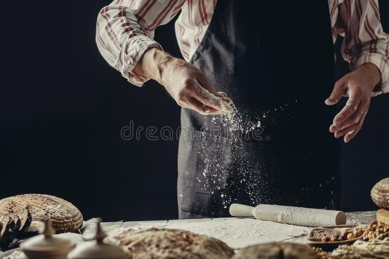 Man sprinkling some flour on dough. Hands kneading dough, cropped view. Male Cook hands kneading dough, sprinkling piece of dough with white wheat flour. Low key stock photo