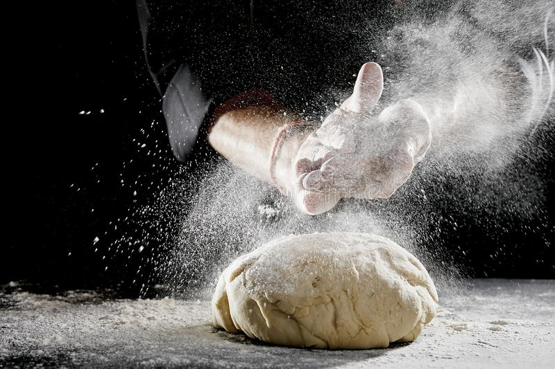 Man sprinkling white flour over blob of dough. Unidentified man wearing black chef suit hidden in the shadows sprinkling white flour over brightly lit blob of stock photography