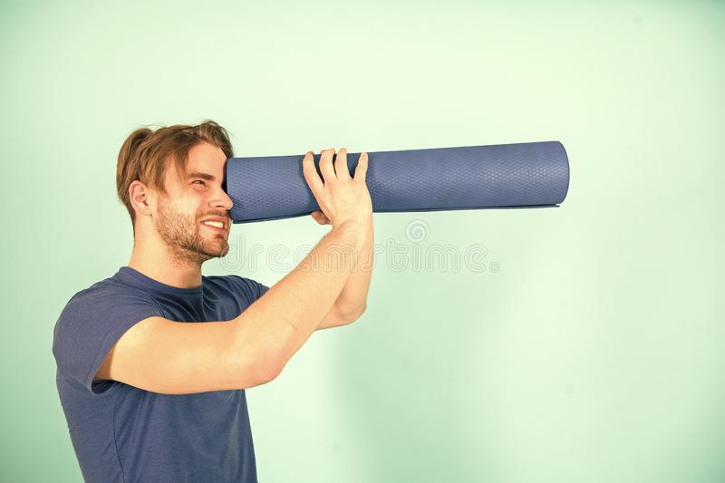 Man spy in yoga mat as telescope. Fashion athlete in blue tshirt and shorts. Sportsman with stylish bristle and hair royalty free stock photos