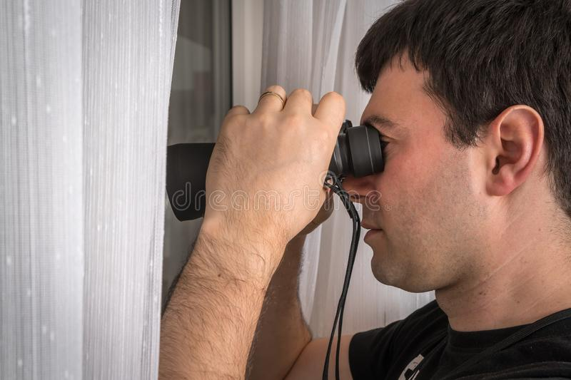 Man is spying his neighbours with binoculars royalty free stock photos