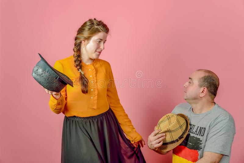 A man is squatting at the bottom, and a woman in a straw hat looks at him from above, posing on a camera in a studio on a red royalty free stock images