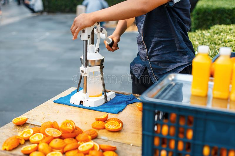 Man squeezes orange juice. Outdoors. royalty free stock images