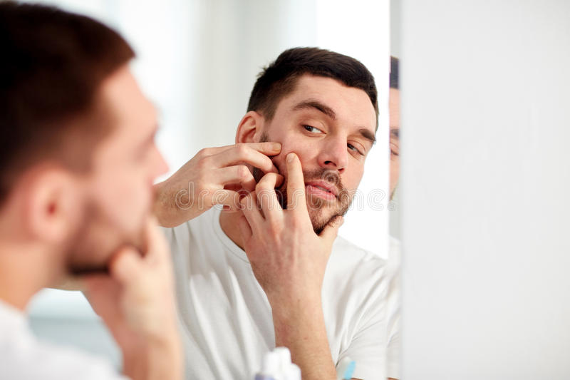Man squeezing pimple at bathroom mirror. Beauty, hygiene, skin problem and people concept - young man looking to mirror and squeezing pimple at home bathroom royalty free stock photo