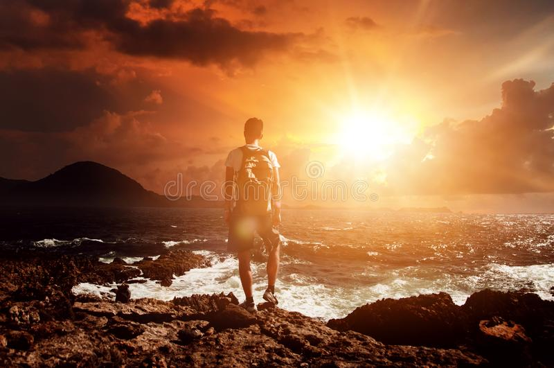 Man står och tittar på en dramatisk orange soluppgång arkivfoton