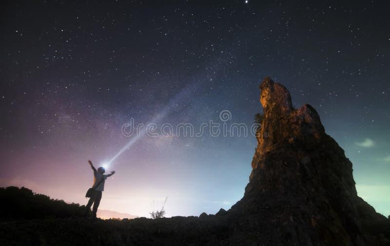 Man staat tussen rotsberg en melkweg stock foto