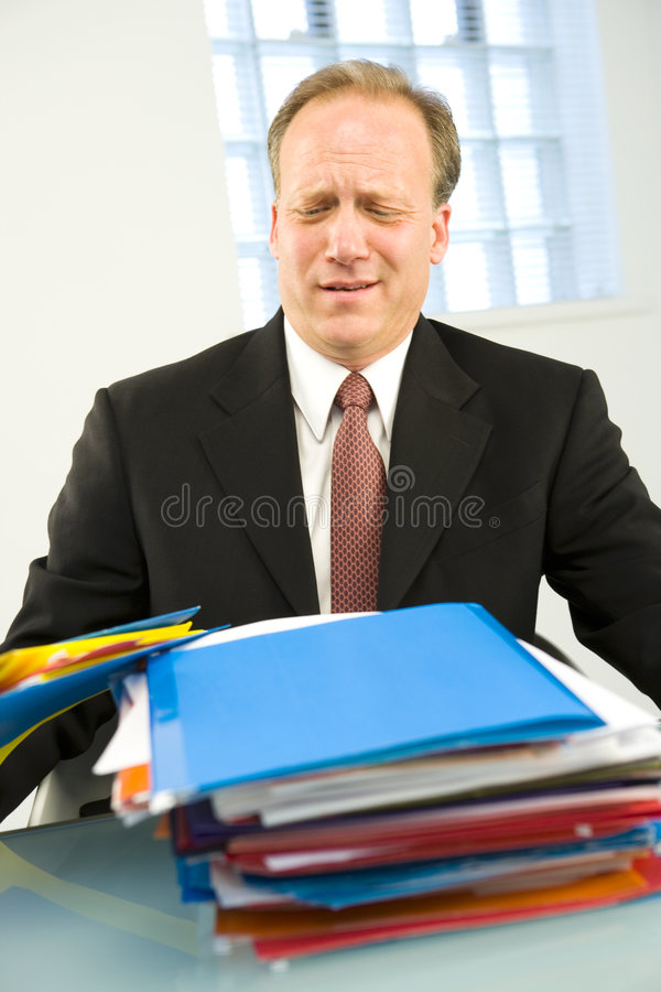 Man with stack of folders. Businessman with overworked expression on face looking at stacks of folders stock photo