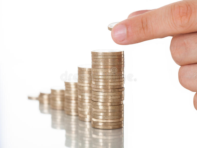 Man stacking coins at desk. Cropped image of man stacking coins at desk against white background stock images