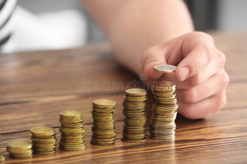 Man stacking coins on table. Savings concept royalty free stock images