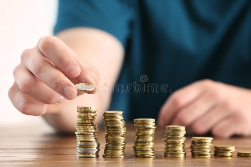 Man stacking coins on table. Savings concept royalty free stock photography
