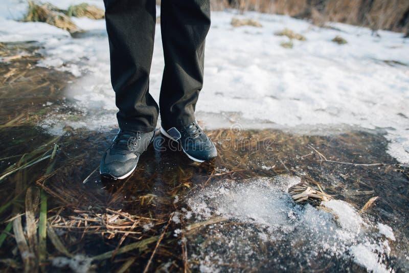 Man staget på den spruckna isen på sjön arkivfoto