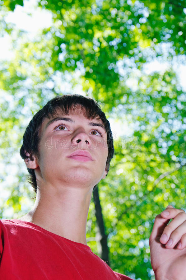 Man stand. Teen look into the distance against the backdrop of greenery stock image