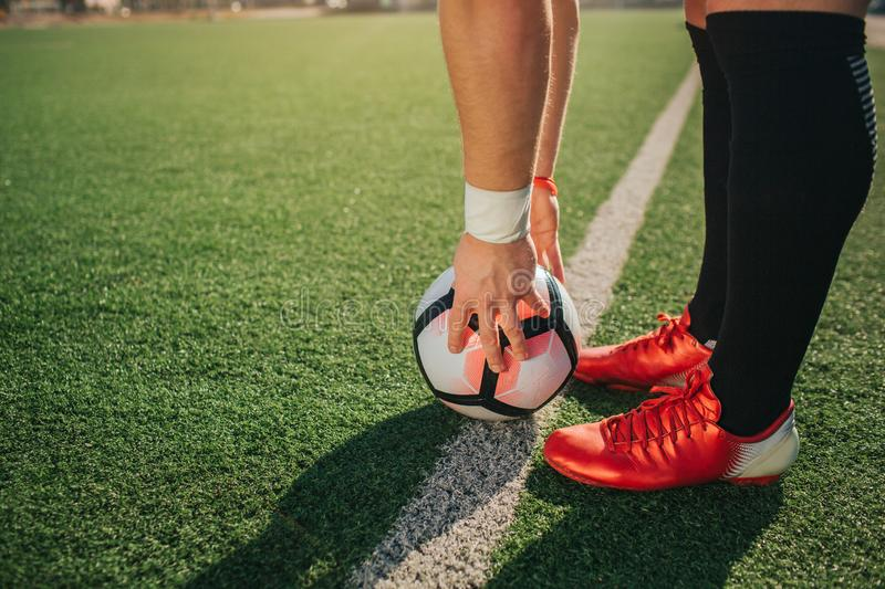 Man stand ar white line painted on lawn. He hold ball on it with hands. Guy wear soccer sneakers. stock photography