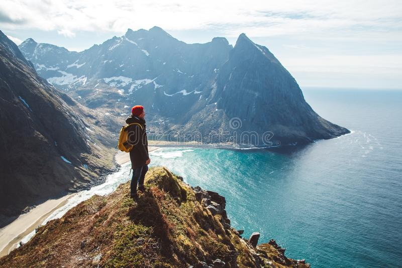 Man stand on cliff edge alone enjoying aerial view backpacking lifestyle travel adventure outdoor vacations.  stock photo