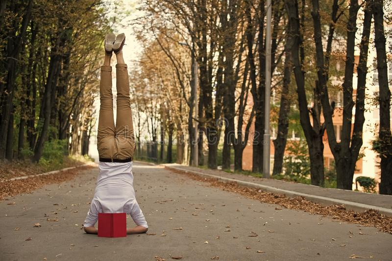 Man stand on head on park road. Student with book upside down in autumn outdoor. Work life balance. Education and. Knowledge. Yoga exercise headstand and sport stock photos
