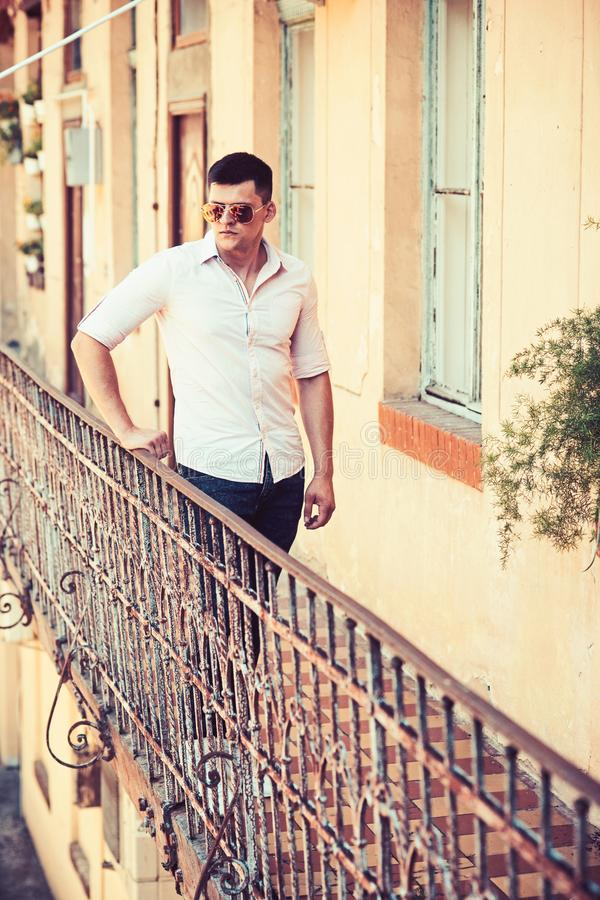 Man stand on house balcony. Macho in fashionable shirt and jeans fashion. Fashion model in sunglasses on terrace. Handsome guy enjoy view on vacation. Youth stock photo