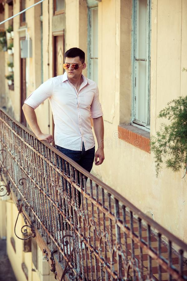 Man stand on house balcony. Macho in fashionable shirt and jeans fashion. Fashion model in sunglasses on terrace. Handsome guy enjoy view on vacation. Youth stock images