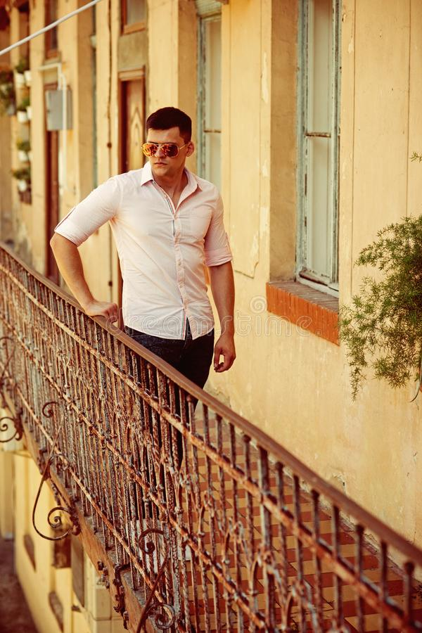 Man stand on house balcony. Macho in fashionable shirt and jeans fashion. Fashion model in sunglasses on terrace. Handsome guy enjoy view on vacation. Youth royalty free stock photography