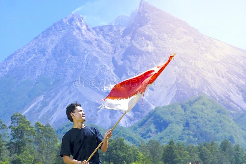 A man stand with Indonesia flag stands with Merapi Mt background. indonesia independence day celebration concept royalty free stock photos
