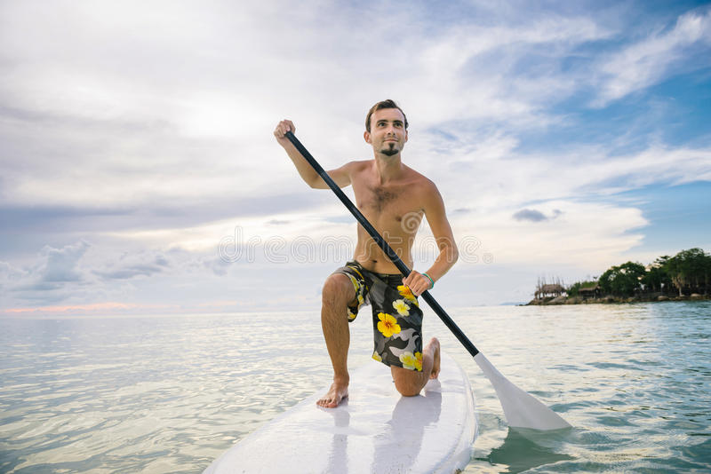 Man stand up on paddle board at sunset stock images