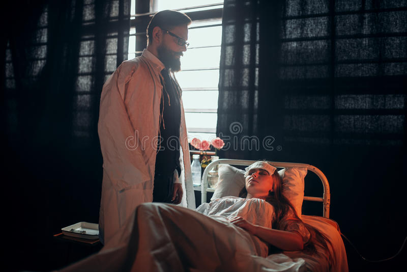Man standing against ill woman in hospital bed royalty free stock photography