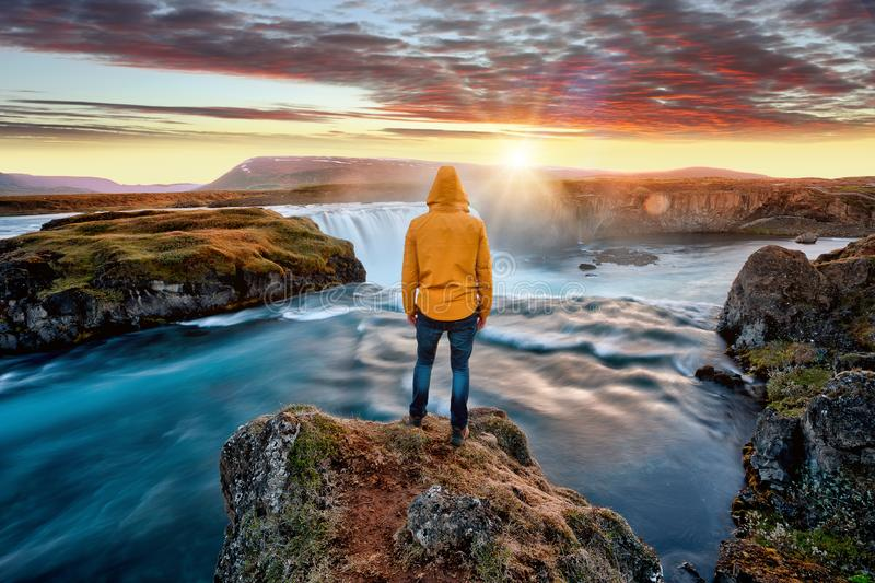 Man standing by amazing Godafoss waterfall in Iceland during sunset stock image