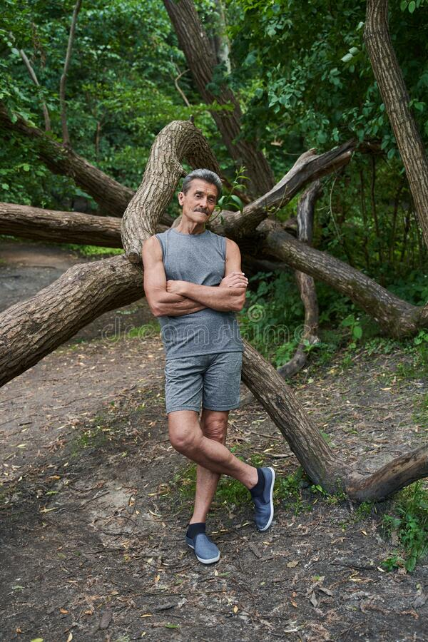 Free Man Standing Arms Crossed Near The Tree And Looking Away While Relaxing Royalty Free Stock Photography - 225336507